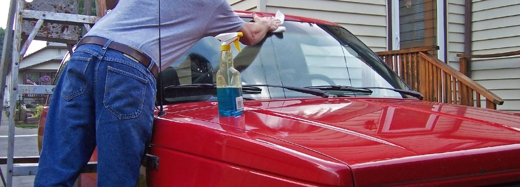 a man cleaning the windshield of his red car