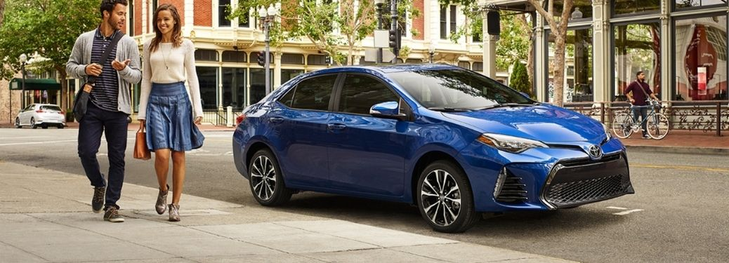Blue 2018 Toyota Corolla in a city scape with a couple beside it