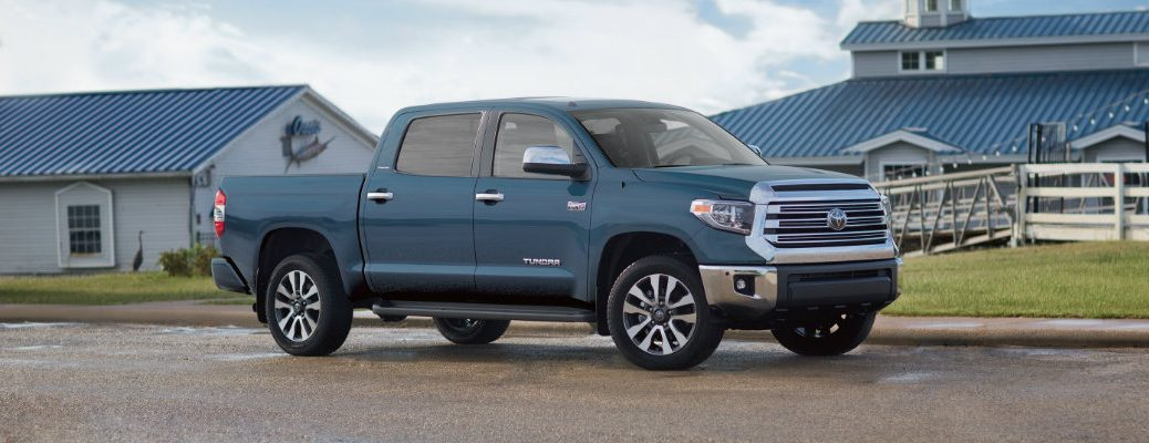 2019 Toyota Tundra exterior side shot with pale blue paint color parked by a waterfront sea dock near a seafood restaurant