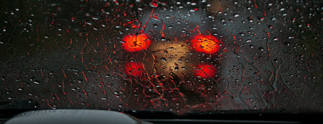 the blured red light of taillights of a car driving in the dark and through rain seen from the inside of another vehicle by the driver