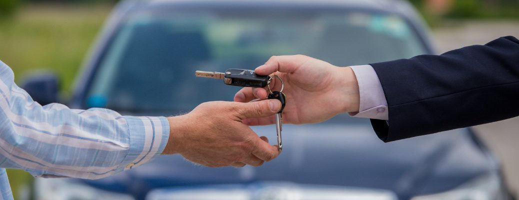 Image of two people exchanging car keys after completing a sales agreement or trade-in agreement