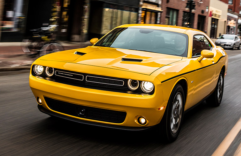 Exterior view of a yellow 2018 Dodge Challenger driving down a city street