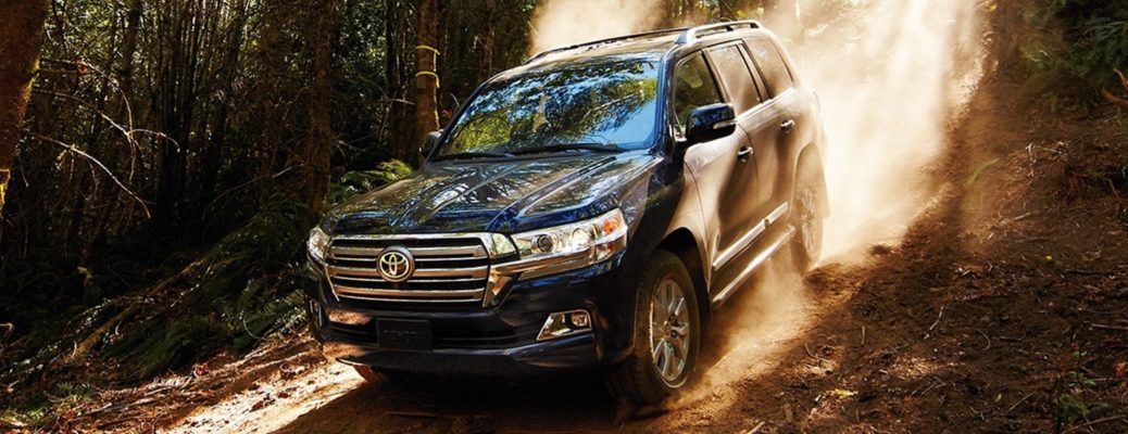Exterior view of a black 2016 Toyota Land Cruiser descending down a dirt path