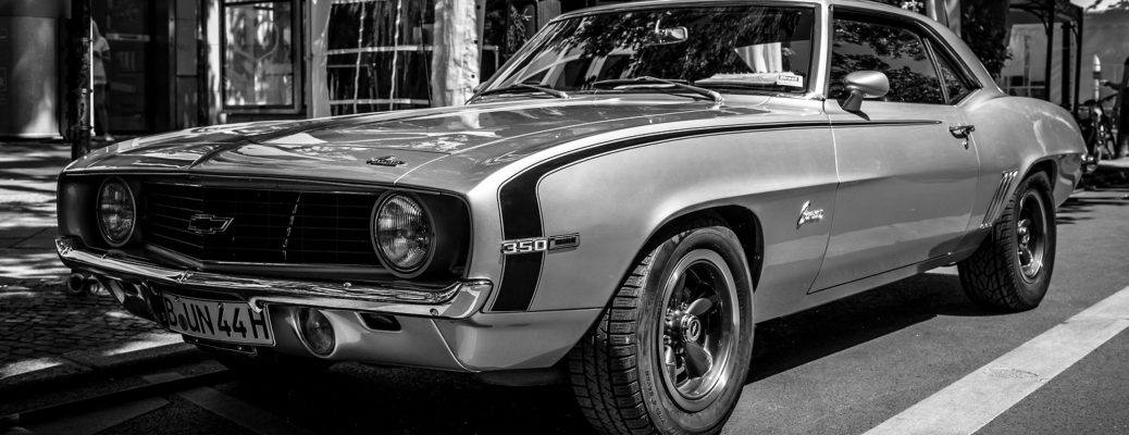 Black and white image of a silver 1969 Chevrolet Camaro Z28 parked on a city street