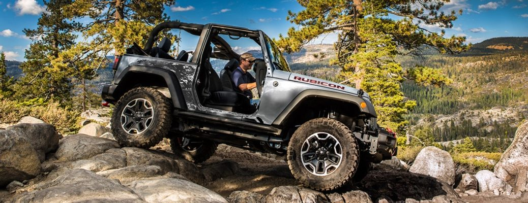 Exterior view of a 2017 Jeep Wrangler driving over rocky terrain