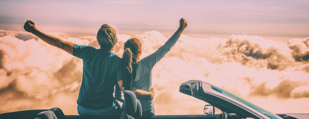 A man and a woman leaning against their car with hands raised as they look out on the rocky terrain on a sunny day