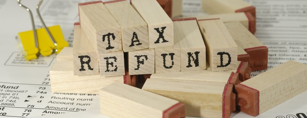 "View of wooden blocks that spell out ""Tax Refund"" sitting on top of tax documents"