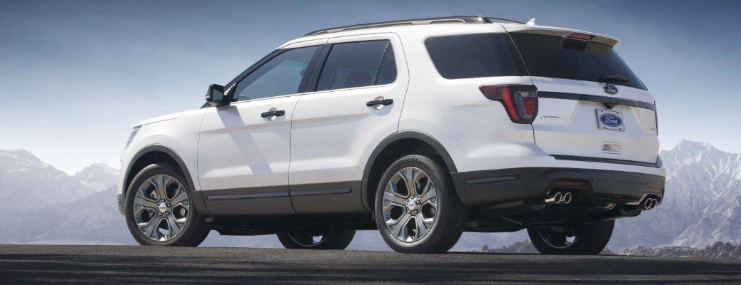 Exterior view of a white 2018 Ford Explorer parked on asphalt with mountains in the background