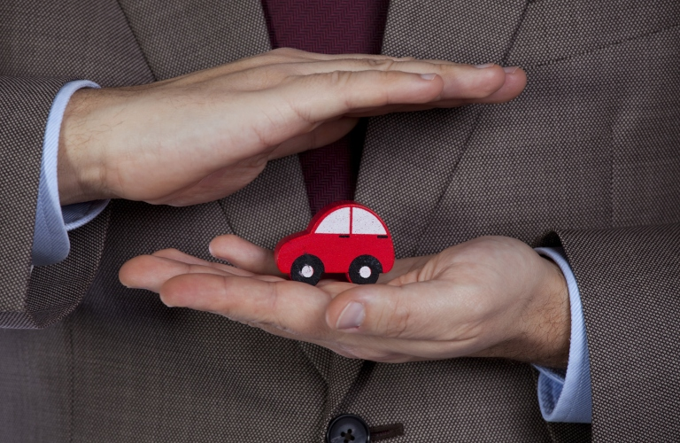Image of a mans hands protecting a small red car toy to signify car insurance