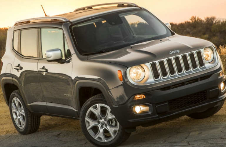 Exterior view of a grey 2017 Jeep Renegade parked on the shoulder of a highway