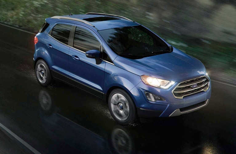 Exterior view of a blue 2018 Ford EcoSport driving down a wet road