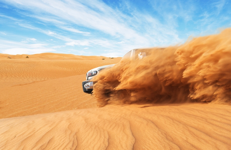 Exterior view of a 4WD SUV driving though the desert spitting up sand all around the vehicle