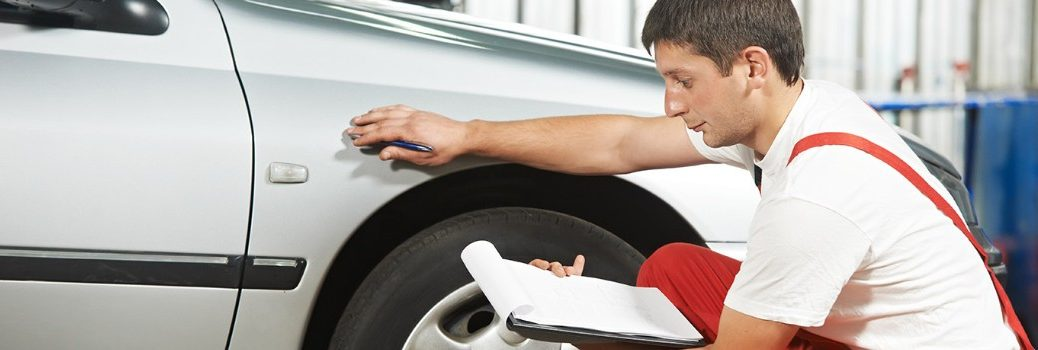 man inspecting a vehicle tire