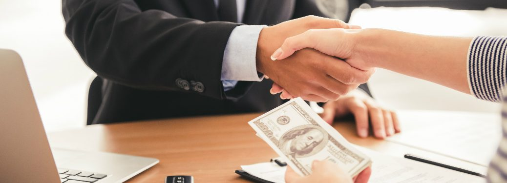 A customer holding money and shaking hands with an associate at a car dealership