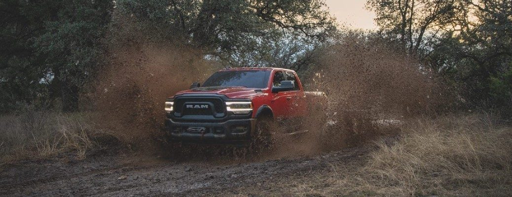 2020 Ram 2500 Red driving through mud with trees in background