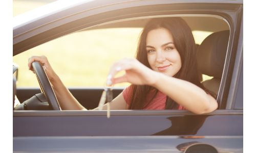 stock photo of woman in car holding keys