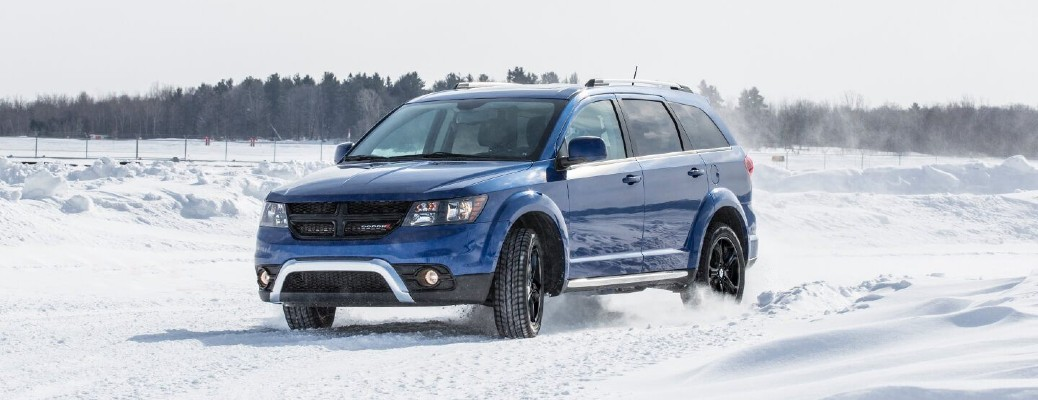2020 Dodge Journey blue driving through snow with trees in background