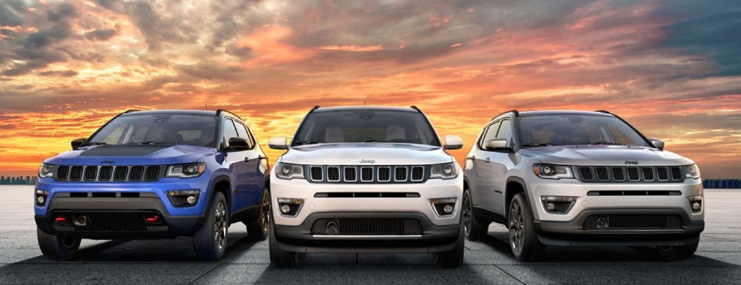 2020 Jeep Compass set of three blue white and gray parked on flat in front of sunset