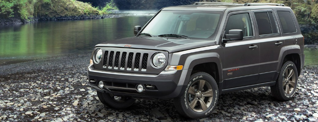2017 Jeep Patriot grey parked on rocks in front of water