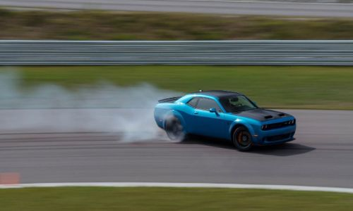 2020 Dodge Challenger hellcat widebody going around a track smoke on tires