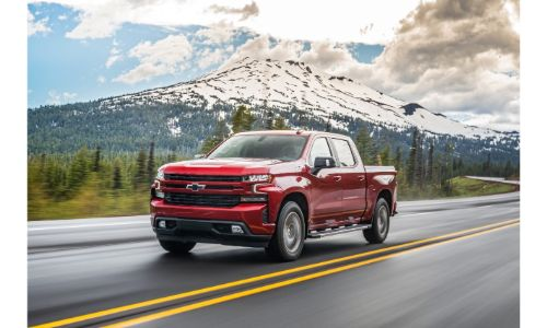 2020 Chevrolet Silverado 1500 red paint driving on road with mountain and clouds in background