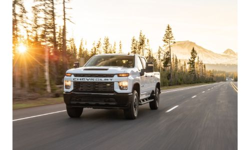 2020 Chevrolet Silverado HD white on side of road with trees most mountains dashed white line and obscured sunlight