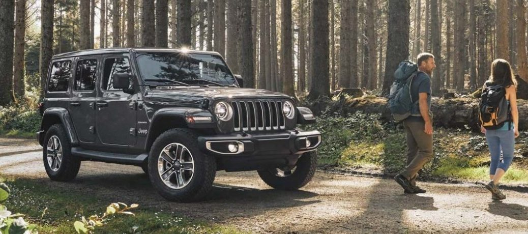 2020 Jeep Wrangler grey parked on forest trail with couple backpacking