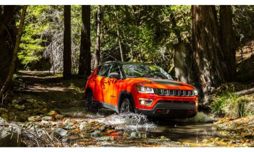 2020 Jeep Compass orange driving through stream in forest