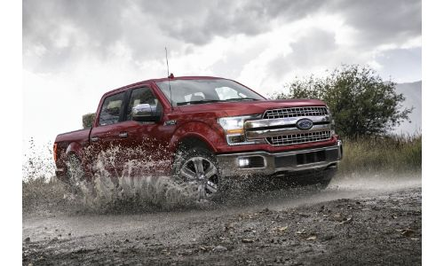 2020 Ford F-150 red paint driving through mud overcast background