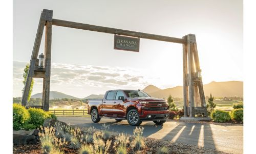2020 Chevrolet Silverado 1500 red distant shot parked under ranch sign sunlight in background