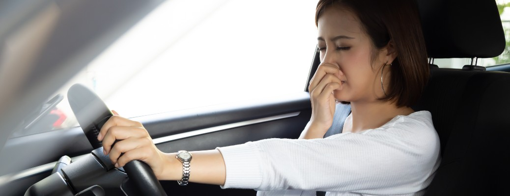 stock photo of woman covering her nose holding steering wheel