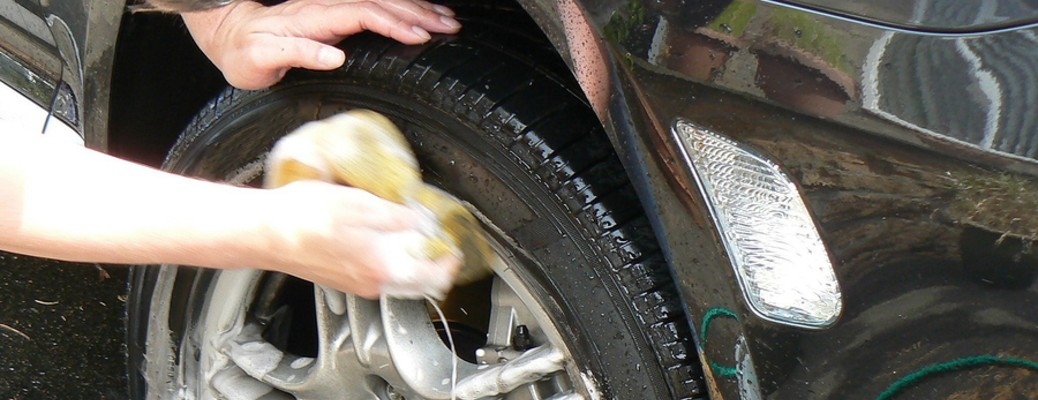 close up of hands washing car tire with sponge and soapy water