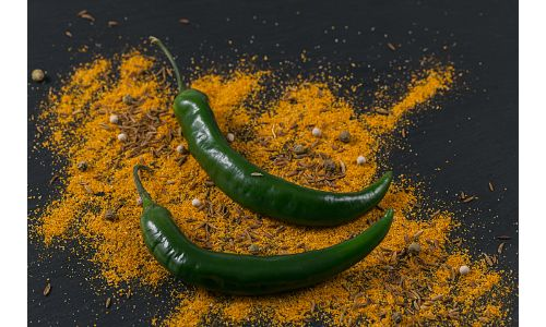green chili peppers resting on spices on table