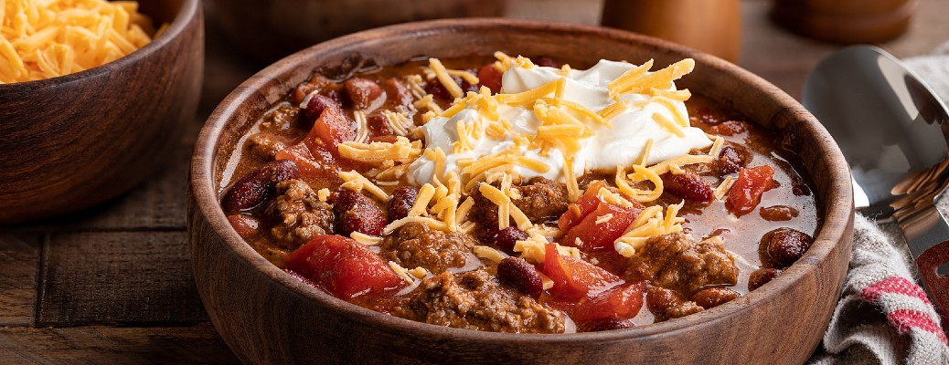 wood bowl of chili with sour cream and cheese