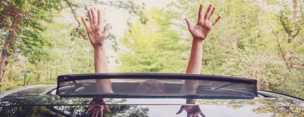 Boy putting his hands outside of a sunroof on sunny day