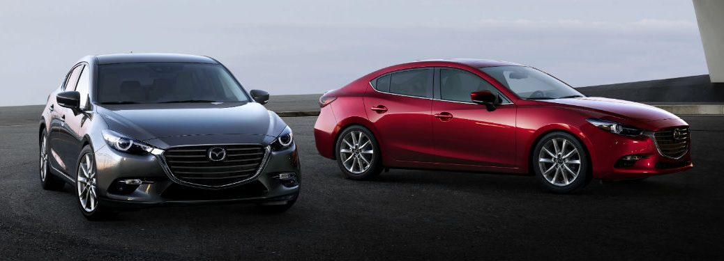 Front exterior view of a gray 2017 Mazda3 Hatchback parked next to a passenger side exterior view of a red 2017 Mazda3 Sedan