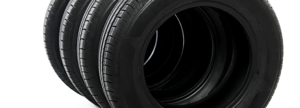 """A row of tires lined up on a white background. We can see through the hole of several of them, making it feel as by looking at this we're on the verge of dropping through the """"portal"""" into some kind of tire-universe."""