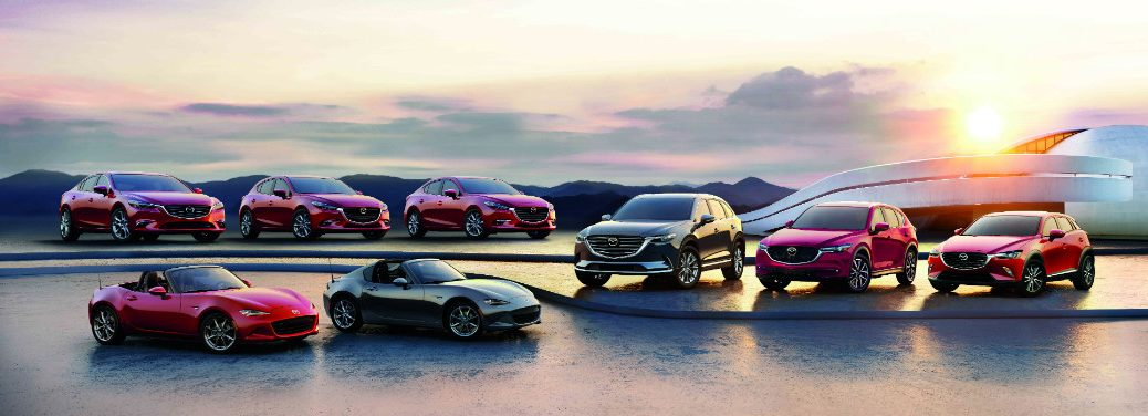A lineup of 2018 Mazda vehicles are arrayed on ice outside of some kind of building.