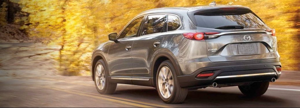 Silver 2019 Mazda CX-9 drives down a country road past some lovely yellow fall trees.