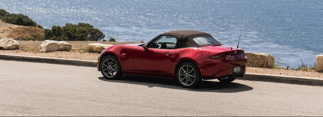 Red 2019 Mazda MX-5 Miata races along the shoreline with its top up.