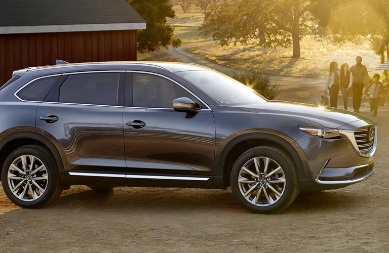 2019 Mazda CX-9 parked by a barn as a family walks toward it out of a beam of sunlight.