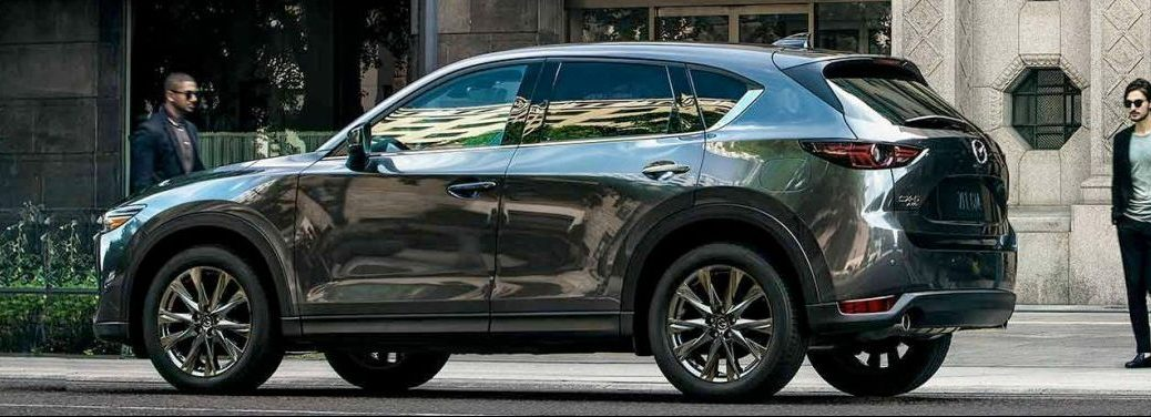 2019 Mazda CX-5 parked in a city as a man walks towards it.
