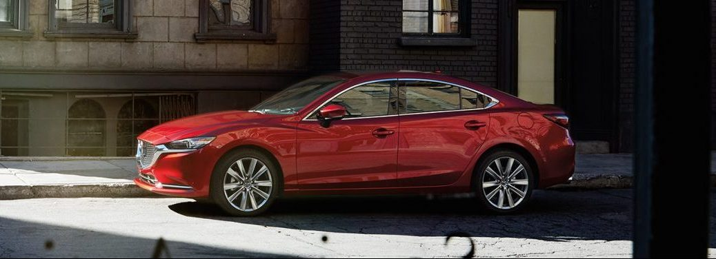 Red 2019 Mazda6, with a heads-up display possibly inside, rolls down a city street.