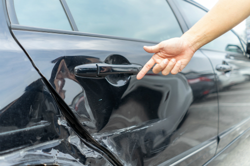 Hand pointing at a dent in rear passenger door and quarter panel