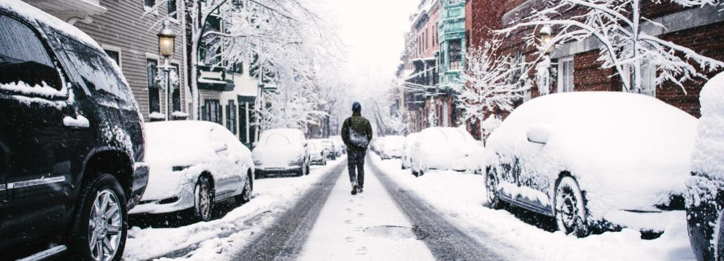 person walking down middle of a snow covered road