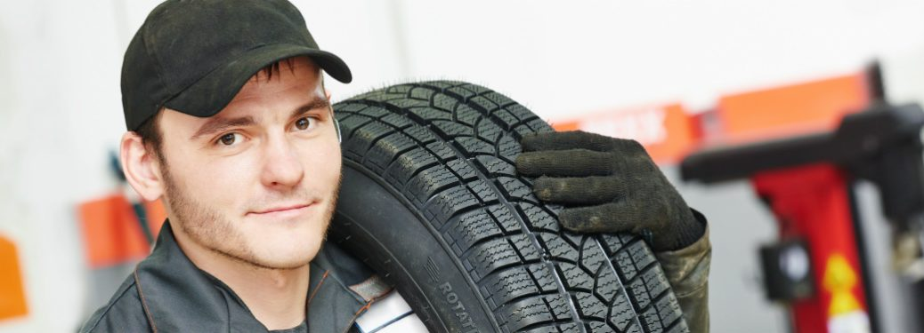 mechanic carrying a tire on shoulder