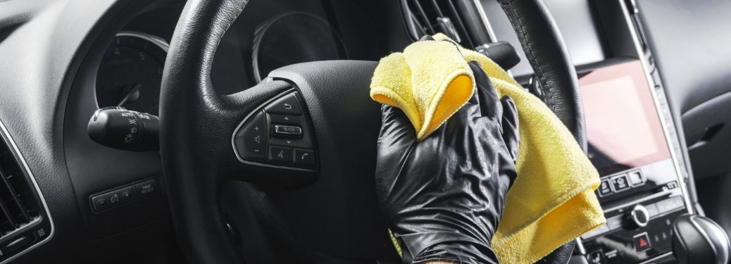 person with gloves cleaning a steering wheel