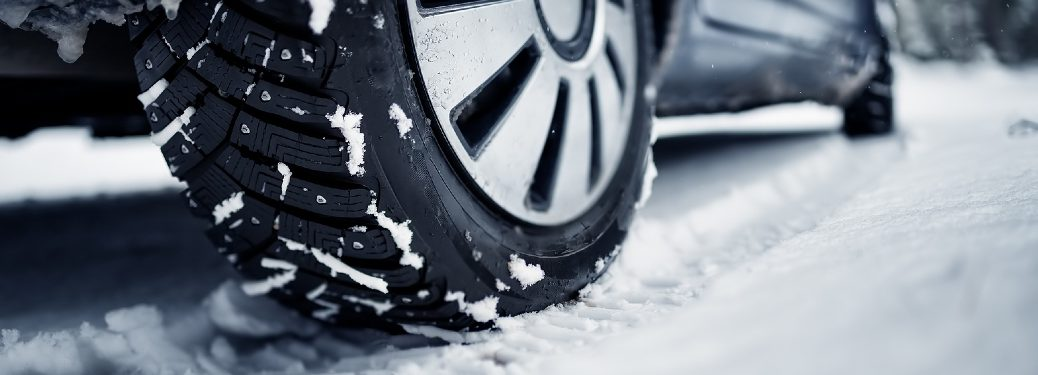 close up on vehicle with snow tries driving in snow