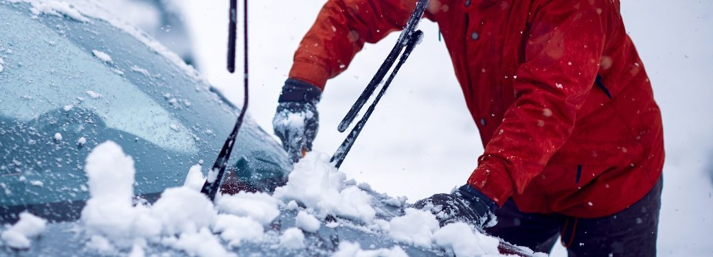 person cleaning snow off car