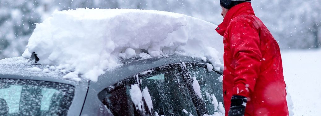 Person clearing snow off car roof